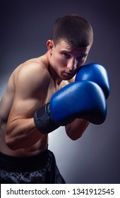Boxing concept. Boxer with boxing blue gloves on a dark background. Studio shot