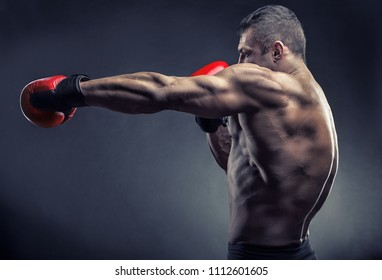 Boxing concept. Boxer with boxing red gloves before a fight on a dark background