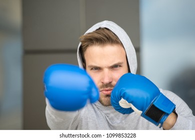Boxing concept. Man athlete on concentrated face with sport gloves practicing boxing punch, urban background. Boxer with hood on head practices jab punch. Sportsman boxer training with boxing gloves.