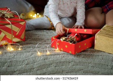 Boxing day. The kid sits among beautifully packed boxes with gifts. He touches the small handles bright Christmas-tree decorations. Merry Christmas and a Happy New Year.