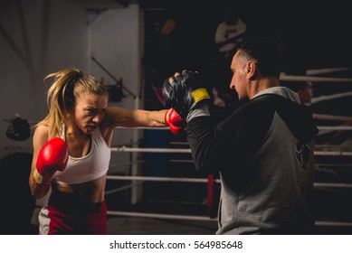 Boxing girl training on boxing mitts held by a master boxer