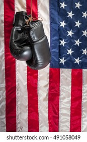 Boxing gloves hanging in dramatic light against the american flag in the background