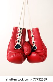 Boxing gloves hanging from laces on a white background.