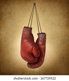 Boxing gloves hanging on an old vintage grunge background with laces nailed to a wall as a business or sport concept of retiring giving up the fight or preparing for competition.