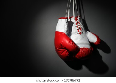 Boxing gloves hanging on wall low key gray background with copy space