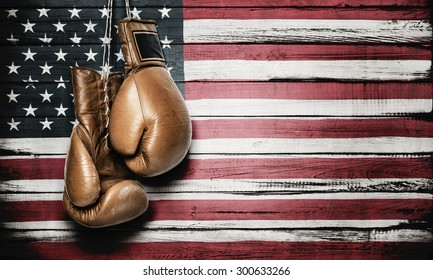 Boxing gloves hanging on wooden wall with American flag