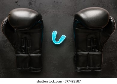 Boxing gloves and a mouth guard on a black background