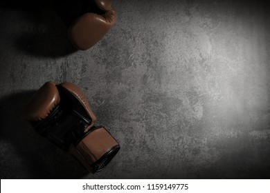 boxing gloves on texture background with copy space. defeat concept.