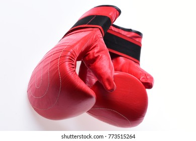 Boxing gloves in red color isolated on white background. Sports and martial arts concept. Pair of boxing gloves lying on each other. Leather box equipment for fight and training.