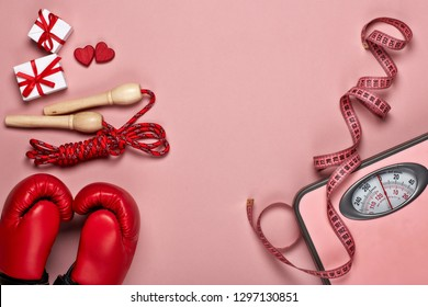 Boxing gloves, skipping rope, scales, gift boxes and red hearts on grey background.Top view with copy space. Valentine's Day card. Fitness, sport and healthy lifestyle concept.