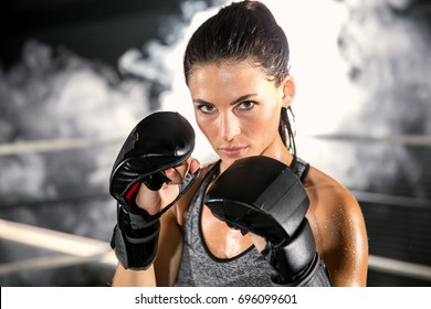 Boxing gym female fighter posing during a cardio fitness workout in a fighting stance