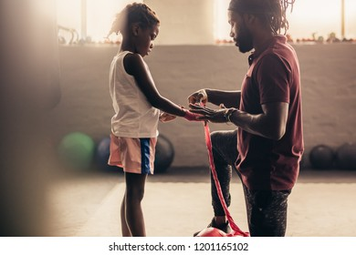 Boxing kid getting his hands wrapped with a bandage before putting on boxing gloves. Side view of a boxing kid with his coach at a boxing gym with sunflare in the background.