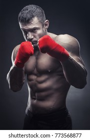 Boxing man ready to fight. Boxer with strong hands and clenched fists in red straps against a black background