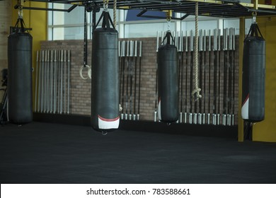 Boxing or Martial arts heavy large punching bags hanging in a gym with barbells and gym rings  in the background,