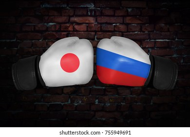 A boxing match. Confrontation between the Japan and Russia. Russian and japanese national flags on Boxing gloves. Sports competition between the two countries. Concept of the foreign policy conflict.