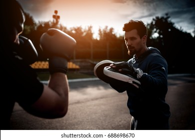 boxing outdoor workout with trainer; punching exercises with personal coach;