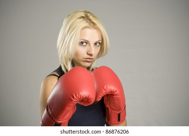 Boxing pose pretty fit blond woman boxer training or working out with red boxing gloves