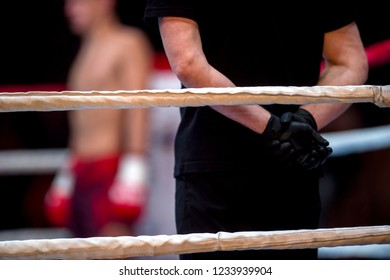 Boxing ring ropes and referee in black clothes in ring two fighters MMA, boxing martial arts competition