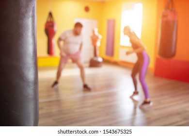 Boxing sparring in training for men and girls under the supervision of a martial arts coach, slow motion, willpower, caucasian, blurred