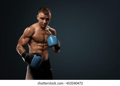 Boxing in studio. Strong boxer posing at camera