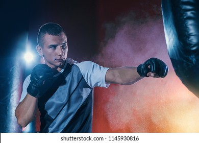 Boxing training. Fighter trains to hit a punching bag in the gym. Young man is an athlete doing workout.