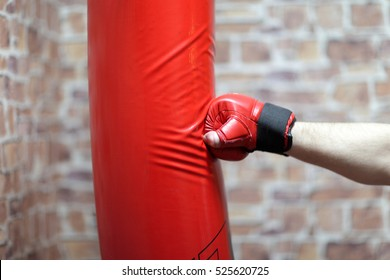 Boxing training - hand and red punching bag