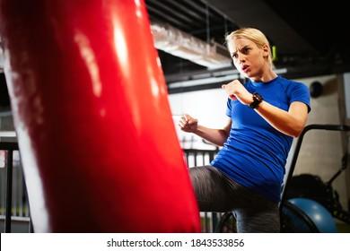 Boxing training woman with punching kicking bag in gym
