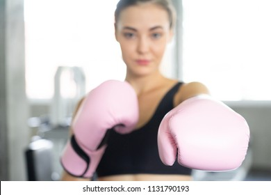 Boxing young beautiful woman exercises with pink glovw.She  doing exercise and punching .