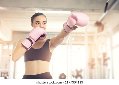 Boxing young beautiful woman exercises with pink glove.She  doing exercise and punching .