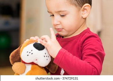 boy 2 years playing with soft toy