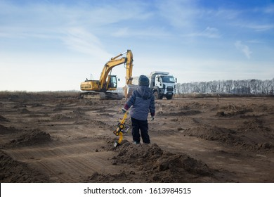 a boy of 3-4 years old in warm clothes at a construction site with his back in the frame holds a toy excavator and looks at the large construction equipment in front of him. Little builder