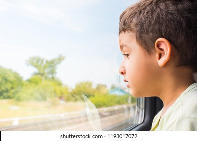 boy 5 years old with interest looking out the window of the train