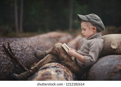 The boy, 5 years old, looks like a trapper, wanderer, lumberjack. Hut, shelter in the forest among logs of wood. A lonely walk, rest after work. Survival.