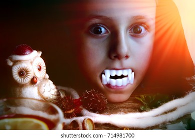 Boy (6-7) dressed as vampire with vampire teeth. Portrait of a child  on a Halloween background with eerie, dramatic light. Halloween concept. Halloween Pumpkin and decorations.