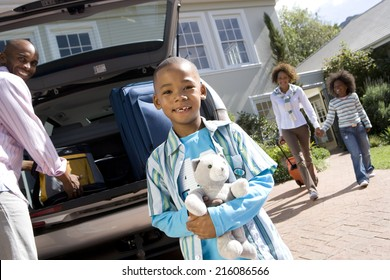 Boy (6-8) with toy by father loading back of car, portrait (tilt)