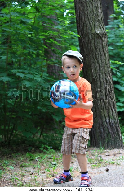 Boy in action young kid playing with ball in park outdoors. Healthy leisure time