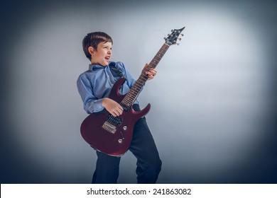 boy adolescence European appearance enthusiastically playing guitar cross process