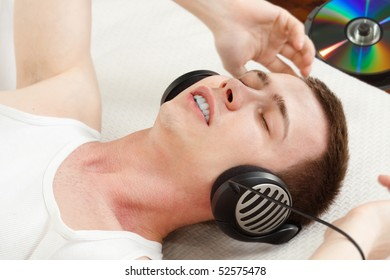 boy adores his favorite music  - headphones on and colorful CD on a background - focus on eyes
