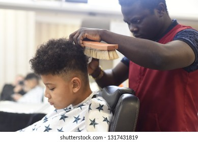 Boy in the african barbershop. Cute mixed boy makes a haircut in the African salon. Hair style. Haircut by machine for children. School boy hair style. Haircut by scissors.
