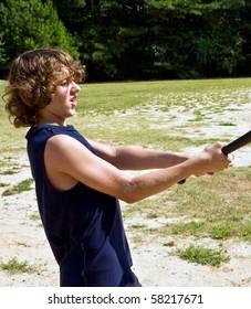 boy, age 12, swinging baseball bat