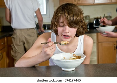 Boy, age twelve, eating breakfast, with father in background