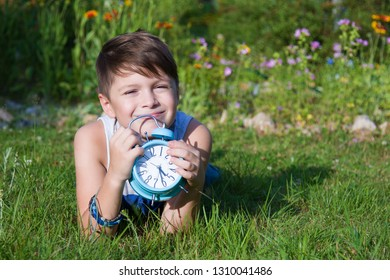 Boy with alarm clock lays in summer garden