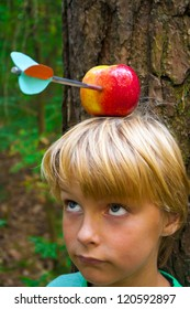 boy with apple on his head, looking up