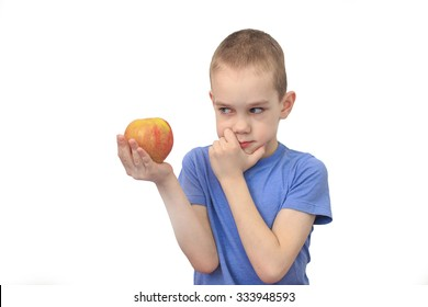 boy with apple. boy thinks looking at apple isolated on white background