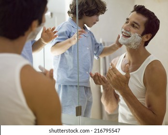 Boy applying shaving foam on his father.