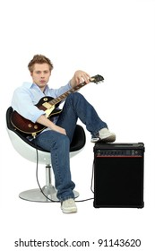 Boy in armchair with guitar and amp