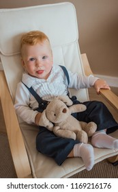 Boy in armchair. A little blond boy sits in an armchair with a plush toy. Emotions of the child