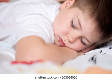 The boy was asleep on a pillow with Chinese characters
