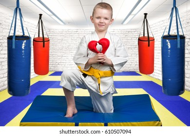 The boy athlete of karate gives a heart made of gloves ,a Declaration of love ,sympathy .Karate on the Mat in the gym.