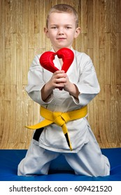 The boy athlete karate gives heart,Declaration of love ,sympathy .Karate on the Mat in the gym.